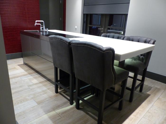 Het werkblad van de keuken is gemaakt van wit corian en net als in de vorige keuken kun je hier aan zitten om bijvoorbeeld je ontbijt te doen.