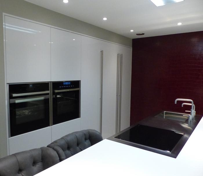 De hoge kasten van de keuken zijn in wit hoogglans lak gespoten.